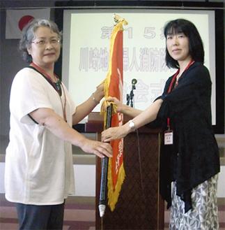 隊旗の受け渡しをする庄司礼子前委員長(左)と澤委員長