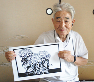自身の作品を掲げる小林代表