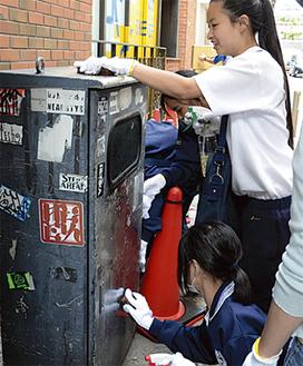 変圧ボックスの落書きを消す中学生