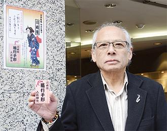 名刺サイズのカードを手にする武藤会長。参加店舗にはポスターが掲示される