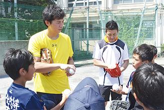 ボールの握り方を指導する内藤さん(左)