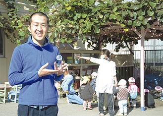 園庭のキウイの木の前でトロフィーを掲げる久保田保育士