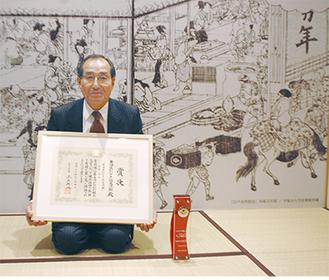 川崎宿の茶屋「万年屋」を再現した同館のお休み処で賞状を手にする青木館長