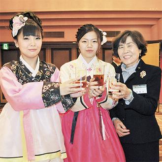 柳菊子民団川崎支部長(右)に祝福される新成人