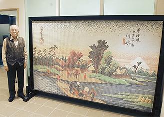 交流館1階に展示されているモザイク画の脇に立つ長田さん(左)
