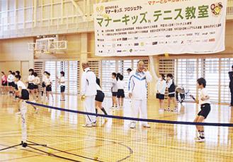 指導者からテニスを教わる児童