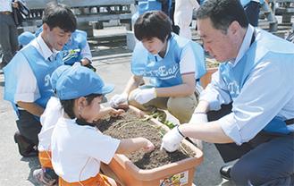 社員と苗を植える園児