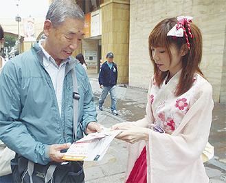 川崎純情小町☆の長嶺あずささん(右)から啓発物を受け取る通行人
