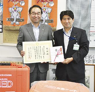 感謝状を手にする岡田代表取締役(左)と伊藤局長