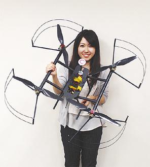 女性が手にする長さ550㎜×幅550㎜×高さ300mmの大型ドローンを製作
