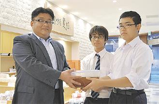 はちみつを手渡す県川高生徒と岩瀬代表取締役(左)
