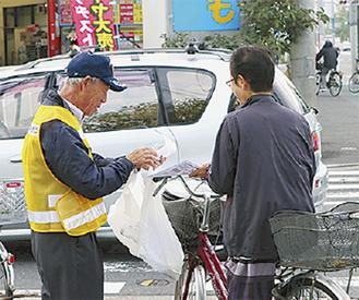 通行人に啓発物を配布するクラブ員(左)