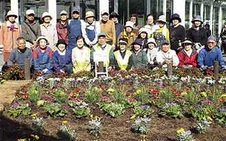 植え替えた花壇の前に集まったフローラかわさきのメンバー