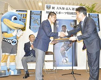 笑顔で表彰状を受け取る大久保選手(中央)