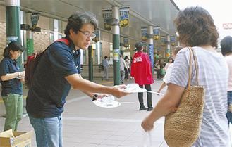 啓発物を配る同会会員(左)