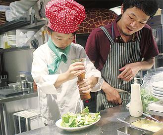 サラダを仕上げを体験する小森田さん
