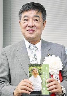 3冊目の著書を手にする飯塚市議
