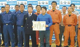 感謝状を受け取る八木さんと馬場署長ら消防隊員
