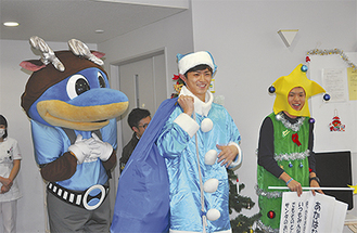 青いサンタクロース衣装をまとう谷口彰悟選手(中央)とふろん太くん(左)