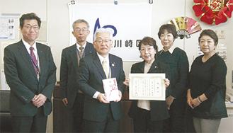 区側(左)と記念写真に納まる大師女連メンバー