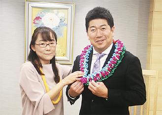 市をイメージしたレイを贈る中野さん(左)