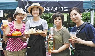 トマトカクテルと手作り料理を持つマルシェのメンバーたち