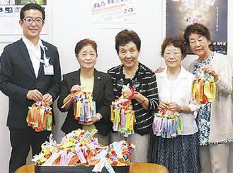 (左から)折鶴を囲む鈴木市民文化局局長と有森幸子委員長