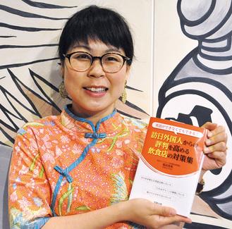 著書を手に笑顔の堀田さん