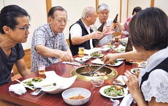 焼き肉を食べながら歓談する年配者ら