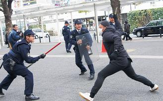 ナイフを持った犯人役(右)に向かう警官たち