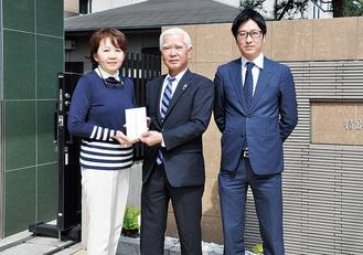 寺尾理事長(左)に寄付金を手渡す石川弘行社長(中央)と純一郎取締役