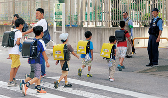 登校時の児童見守り=先月、多摩区