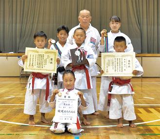 賞状やメダルを手にする道場生と佐々木代表(中央)