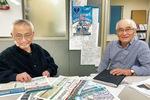 資料を手に取材に応じる昼間事務局長(右)と同会会員