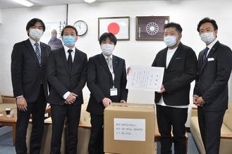 マスクの段ボールの前に立つ石崎さん(右から2番目)ら