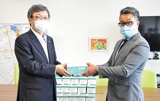 関区長にマスクを手渡す皿嶋支部長(右)