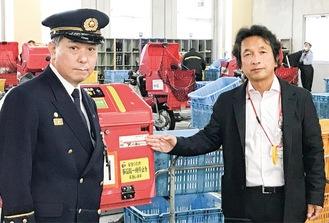 交付されたステッカーを前に立つ宮崎局長 菅野署長(右から)
