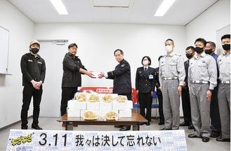 菅野署長(左から3番目)に特製ハンバーガーを手渡す松丸代表