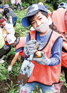 ジャガイモを手に笑顔の児童