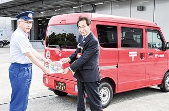ステッカーを手にする小川署長と小松崎局長(左から)