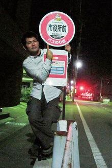 市役所前バス停で喜ぶ飯島さん 昨年9月 =本人提供
