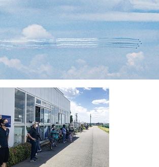 隊列を組んで飛ぶ6機のブルーインパルス=川崎河港水門近くから撮影(上)と、日陰で飛行を待つ人たち=「御幸公園前」信号付近の土手