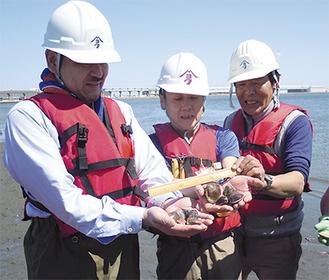 採れたハマグリを手に乗せ、サイズを計る多摩川クラブのメンバー(右が中本さん/多摩川クラブ提供)
