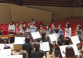 楽団員を前にプレゼンテーションをする児童ら
