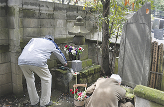戦災殉難者供養塔に花を手向けた。右側の石碑には延命寺に運ばれた犠牲者の名前が刻まれている