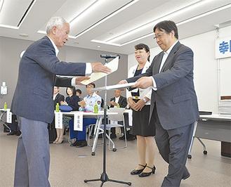 受賞者に表彰状を渡す上野区長と鏑木会長(右)