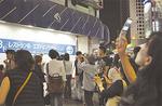 閉店を惜しみ、携帯電話などで店を撮影する人たち