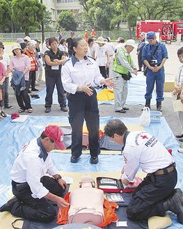 AEDの使い方を参加者に教える赤十字関係者