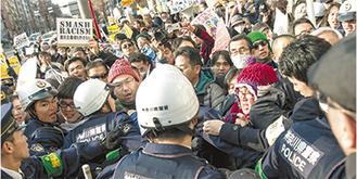 反ヘイトの抗議活動の最中警官ともみ合いにある市民(撮影/ヤベシンタ)