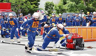 ホースを肩に背負い放水の準備をする消防団員